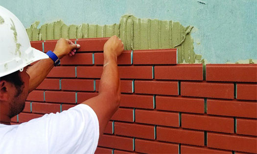 worker applying new brick to a building